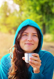 Young woman holding cup of coffee or tea and smiling. Royalty Free Stock Image