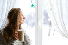 Young woman holding cup of tea in hands, looking through the window Royalty Free Stock Photo