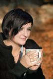 Young woman holding cup of tea outdoor Stock Photography