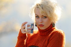 Young woman holding cup of tea outdoor Royalty Free Stock Photography