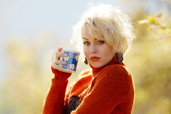 Young woman holding cup of tea outdoor Royalty Free Stock Images