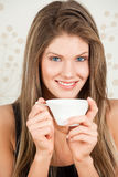 Young woman holding a cup of tea and smiling Stock Photo