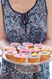 Young woman holding cupcakes plate Royalty Free Stock Photography