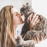 Young woman holding a cute, adorable kitten royalty free stock image