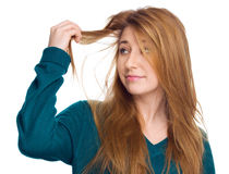 Young woman holding damaged long hair the hand and looking at split ends, isolated on white Royalty Free Stock Images