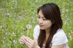 Young woman holding dandelion Royalty Free Stock Photos
