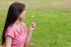 Young woman holding a dandelion while sitting in the countryside Stock Photos