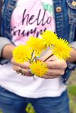 Young woman holding a dandelions bouquet in the green park at spring time. Bright and fresh flower background. royalty free stock images