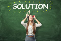 Young woman holding different office supplies in hands and standing under the word'solution' written above her head. A young woman holding different office royalty free stock photo