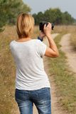 Young woman holding digital camera and taking pictures. Of the summer landscape at rural road Royalty Free Stock Photos