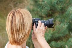 Young woman holding digital camera and taking pictures Stock Photos