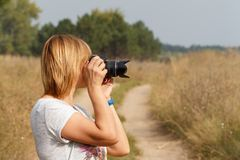 Young woman holding digital camera and taking pictures. Of the summer landscape at rural road Royalty Free Stock Images
