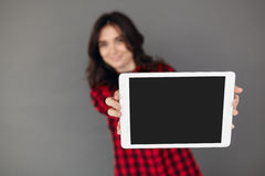 Young woman holding digital tablet computer. Shallow depth of field. Focus on tablet. Young woman holding digital tablet computer isolated on grey background Stock Photo
