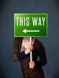 Young woman holding a direction sign Stock Image