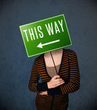 Young woman holding a direction sign Stock Photo