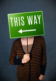 Young woman holding a direction sign Royalty Free Stock Photo