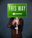 Young woman holding a direction sign Stock Photos