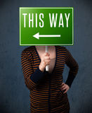 Young woman holding a direction sign Royalty Free Stock Photos