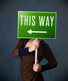 Young woman holding a direction sign Royalty Free Stock Images