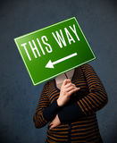 Young woman holding a direction sign Stock Photography