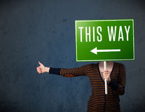 Young woman holding a direction sign Royalty Free Stock Photography