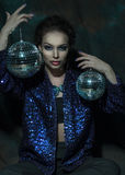 Young woman holding disco ball Stock Photo