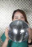 Young woman holding a disco ball, looking at camera in front of shiny wall Royalty Free Stock Photos