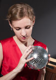 Young woman holding disco ball sitting on grey background Stock Image