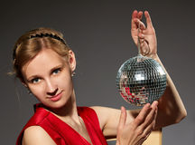 Young woman holding disco ball sitting on grey background Stock Images