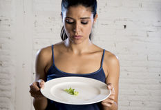 Young woman holding dish with ridiculous lettuce as her food symbol of crazy diet nutrition disorder Royalty Free Stock Photo