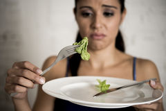 Young woman holding dish with ridiculous lettuce as her food symbol of crazy diet nutrition disorder Stock Images