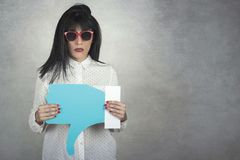 Young Woman holding a dislike icon. On gray background royalty free stock photo