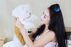 Young woman holding dog on the bedroom. Picture of pretty young woman is holding and smiling with her Maltese dog while sitting on the bedroom Royalty Free Stock Photo