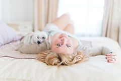 Young woman is holding a dog while laying on a bed Royalty Free Stock Photos