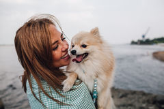 Young woman is holding dog outdoors Royalty Free Stock Photos