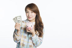 Young woman holding dollars and piggy bank, savings imagery Royalty Free Stock Photos