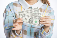 Young woman holding dollars and piggy bank, savings imagery Stock Image