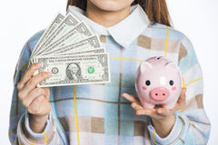 Young woman holding dollars and piggy bank, savings imagery Stock Photos