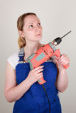 Young woman holding a drilling machine in her hands Royalty Free Stock Photo