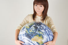 Young woman holding earth ball. Looking at camera Royalty Free Stock Images