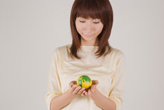 Young woman holding earth ball. Looking down Stock Photos