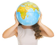 Young woman holding earth globe in front of face Royalty Free Stock Photos