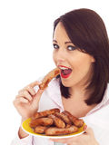 Young Woman Holding  Eating a Plate of Pork Sausages Royalty Free Stock Image
