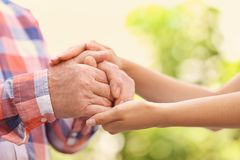 Young woman holding elderly man hands stock photo