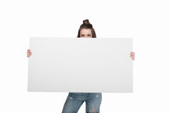 Young woman holding empty banner and looking at camera,. Isolated on white Stock Photo