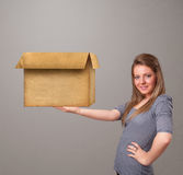 Young woman holding an empty cardboard box Stock Photos