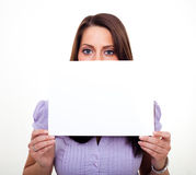 A young woman, holding an empty paper. A young woman, smiling and holding an empty paper in her hands Royalty Free Stock Image