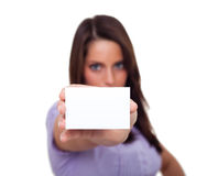 A young woman, holding an empty paper. A young woman, smiling and holding an empty paper in her hands Royalty Free Stock Photo