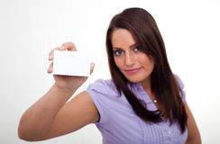 A young woman, holding an empty paper. A young woman, smiling and holding an empty paper in her hands Stock Photography