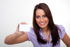 A young woman, holding an empty paper. A young woman, smiling and holding an empty paper in her hands Stock Photo